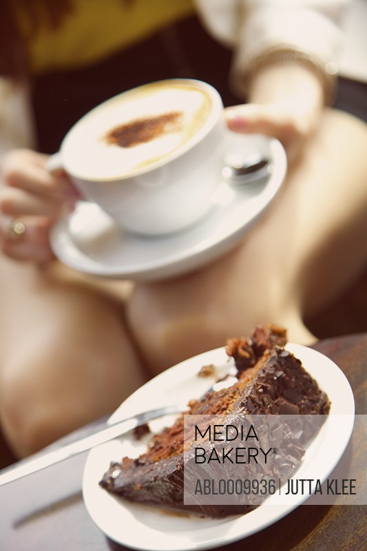 Woman Having Cappuccino and Chocolate Cake, Cropped View