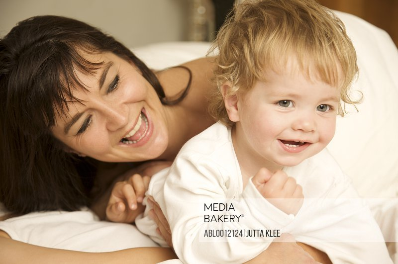 Woman and a toddler hugging and smiling in bed