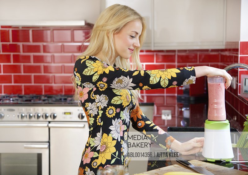 Young Woman Using Blender in Kitchen