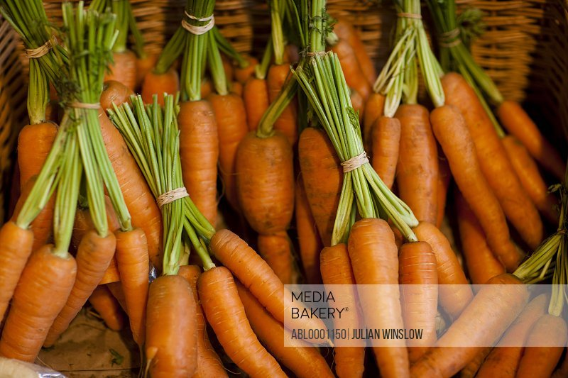 Close up of a basket filled with trimmed bunches of carrots