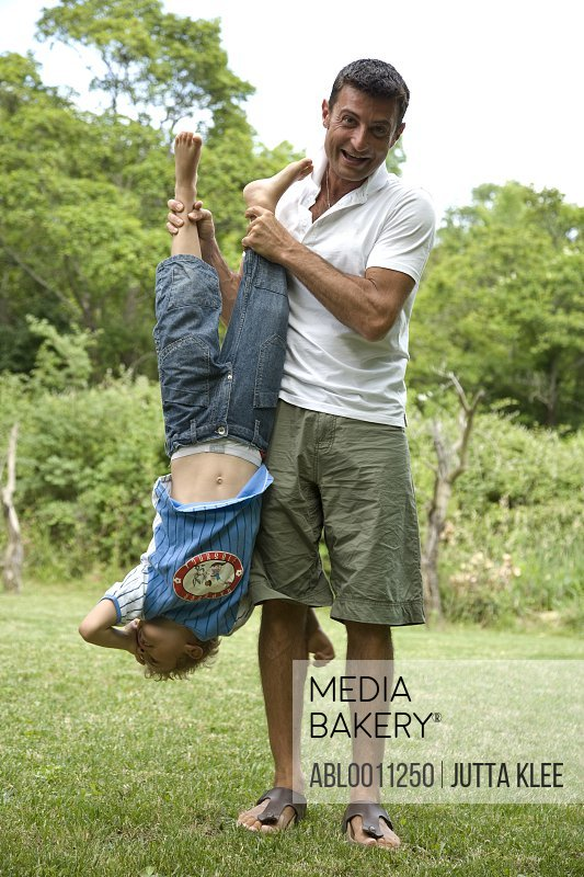 Father holding son upside down in garden