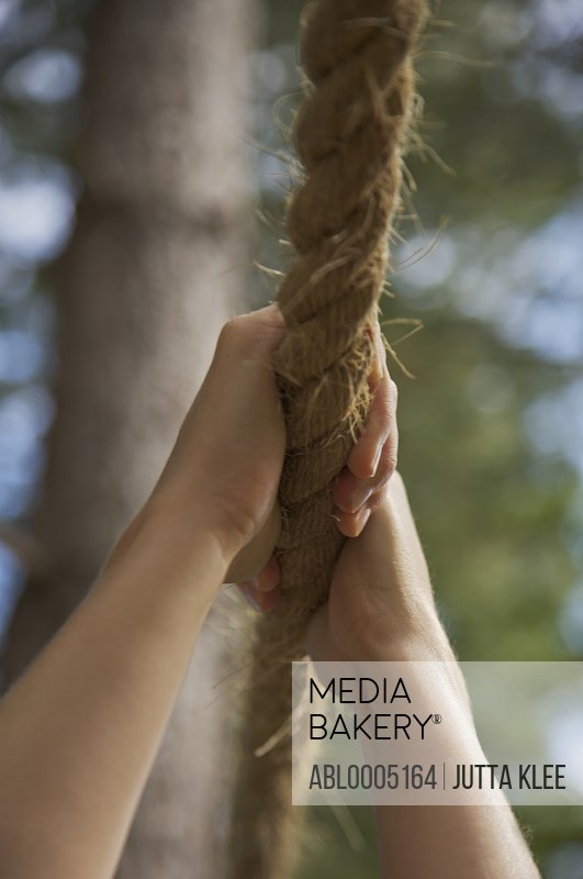 Close up of a woman hands hanging from a rope