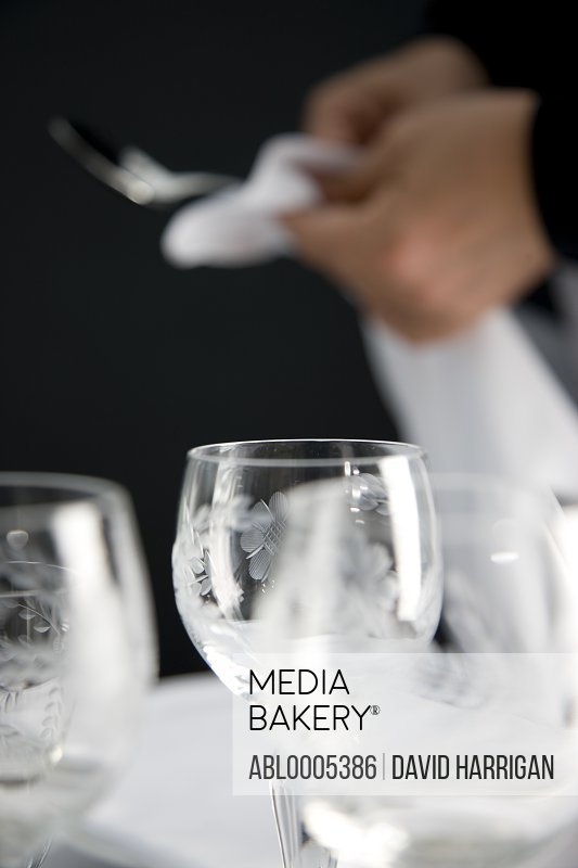 Close up of a waiter hands polishing cutlery standing behind a restaurant table laid out with wine glasses