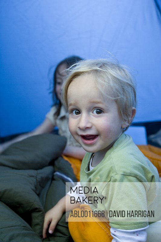 Young boy sitting inside tent smiling