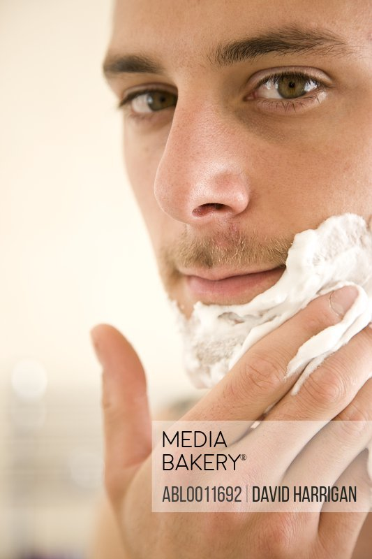Close up of young man applying shaving cream