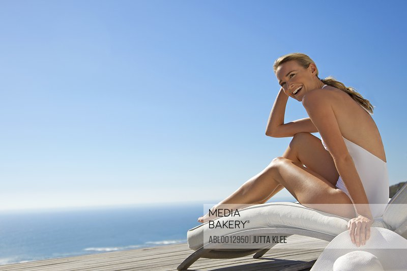 Woman sitting on a sun lounger laughing