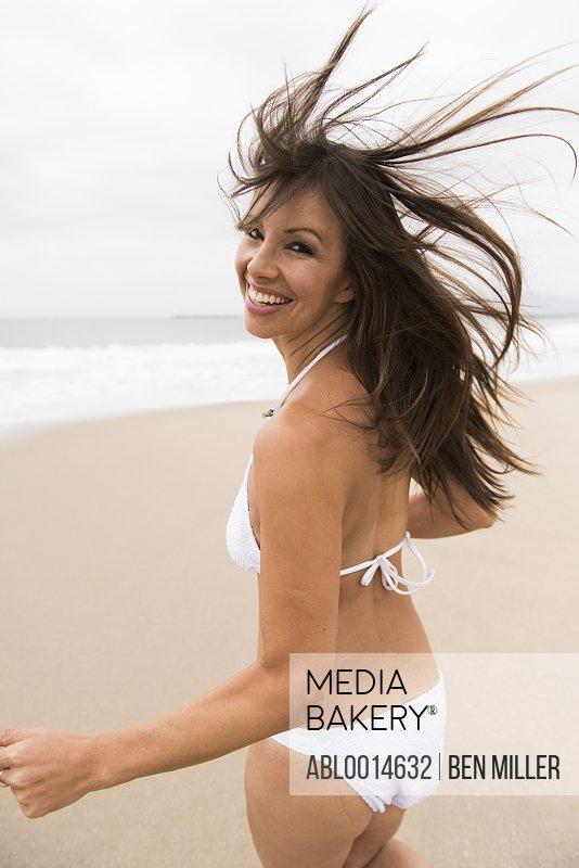 Woman Wearing Bikini Walking on Beach Smiling