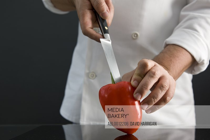 Close up of a chef hand holding a red pepper and removing the core with a knife