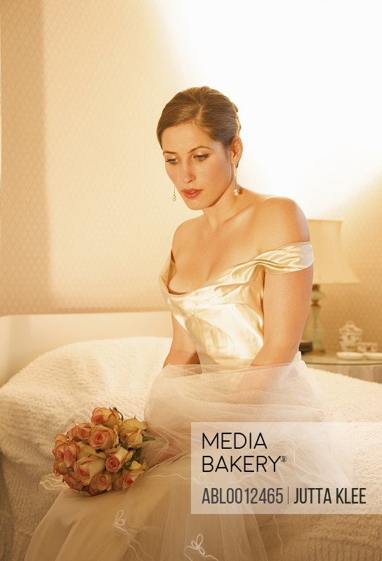 Bride in a white wedding gown sitting on a bed holding a bouquet of roses