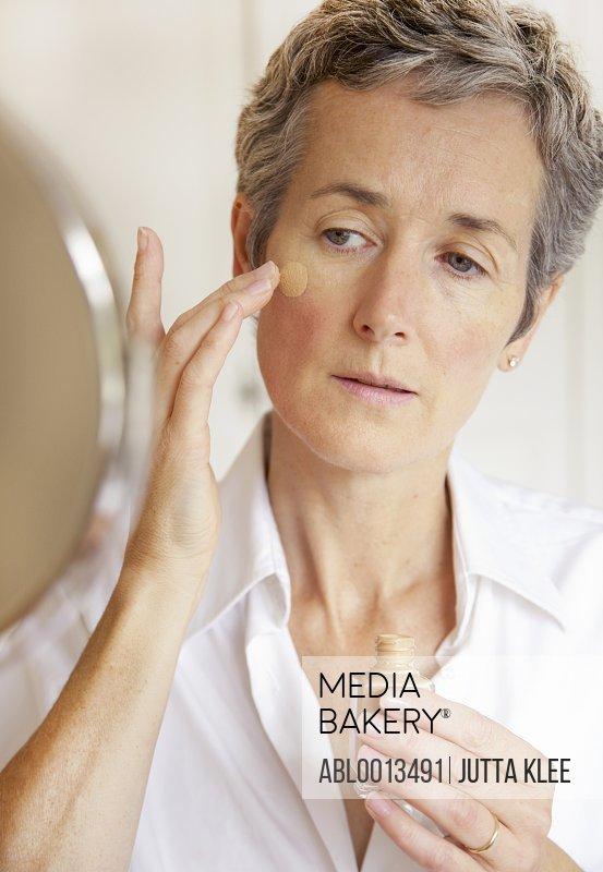 Woman Looking in Mirror Applying Foundation