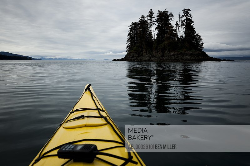 Bow of Yellow Kayak with Walkie-Talkie Moving towards Small Island