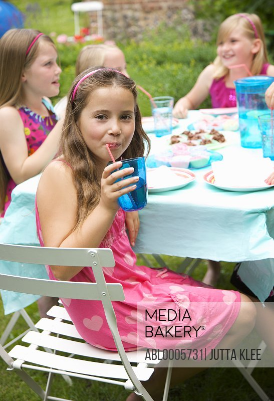 Young girl drinking from a straw at a garden party