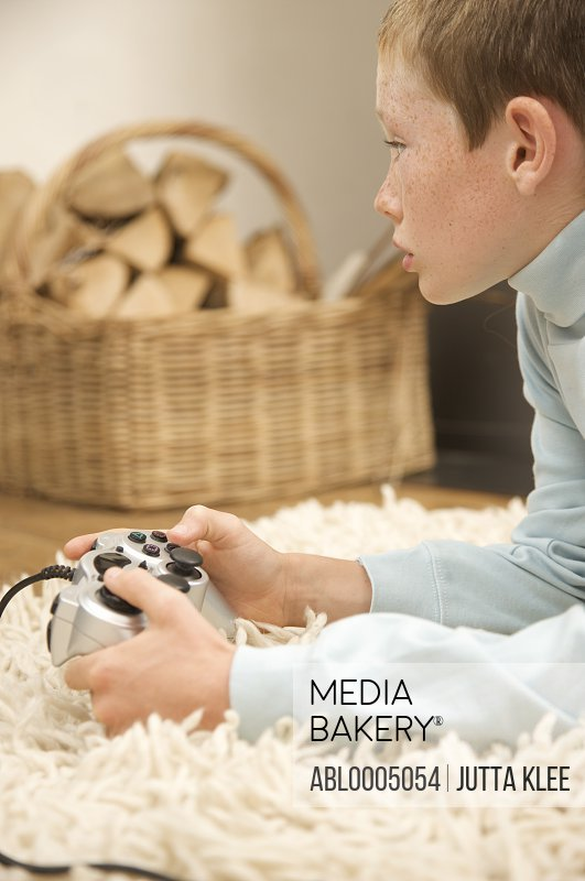 Profile of a young boy lying on a rug and holding a video game control