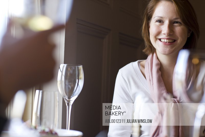 Woman sitting at a dining  table smiling