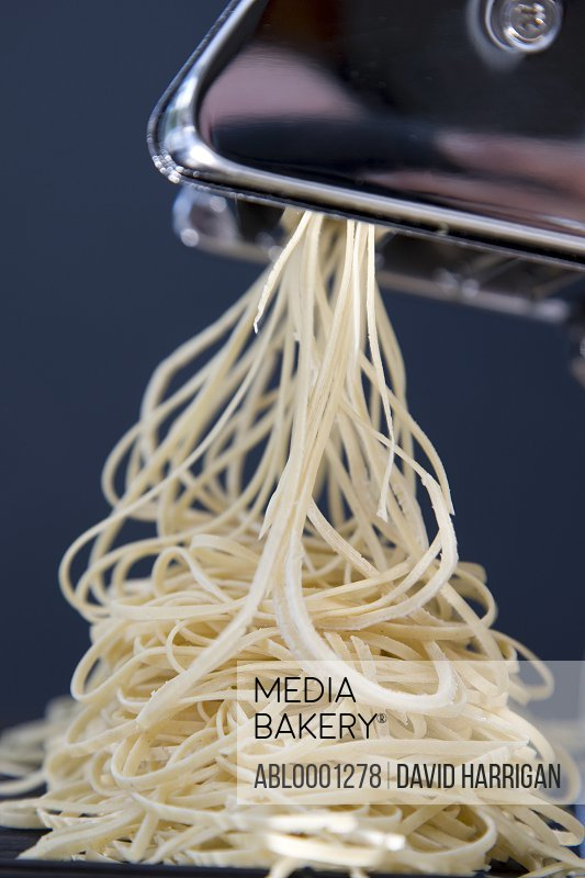 Heap of fresh tagliolini coming out of a pasta maker