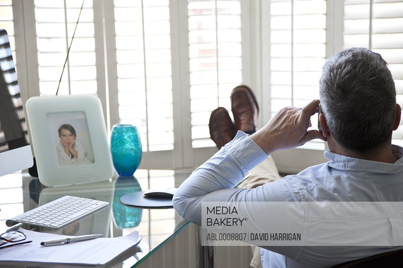 Man at Desk with Feet Up Using Cell Phone, Rear View