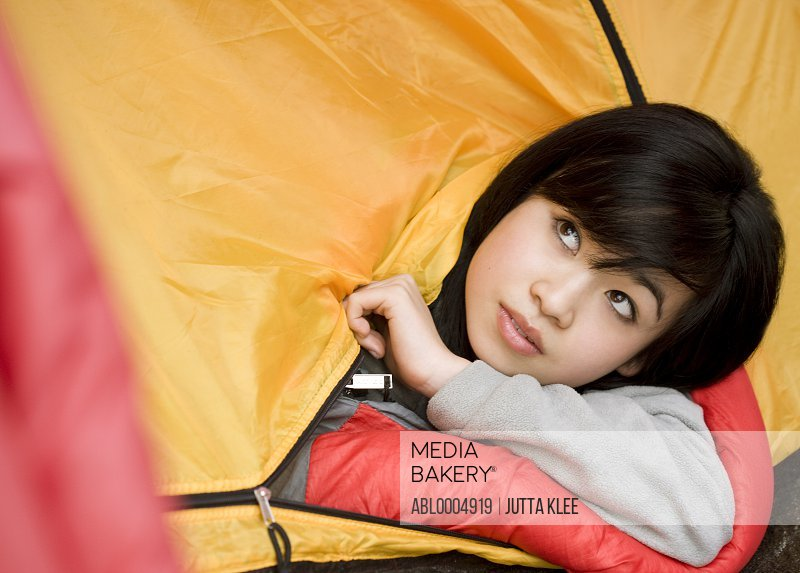 Close up of  teenaged girl head coming out of tent entrance
