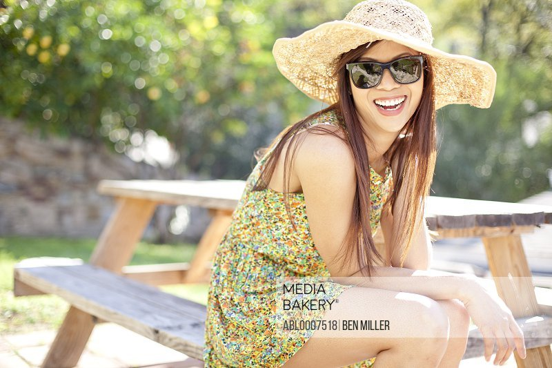 Smiling Woman Wearing Straw Hat Sitting on Picnic Table