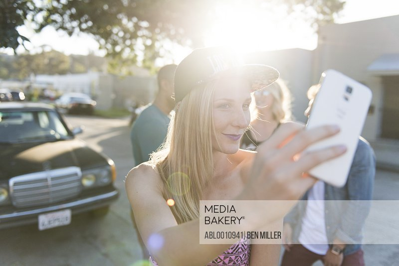 Smiling Woman Taking a Group Selfie
