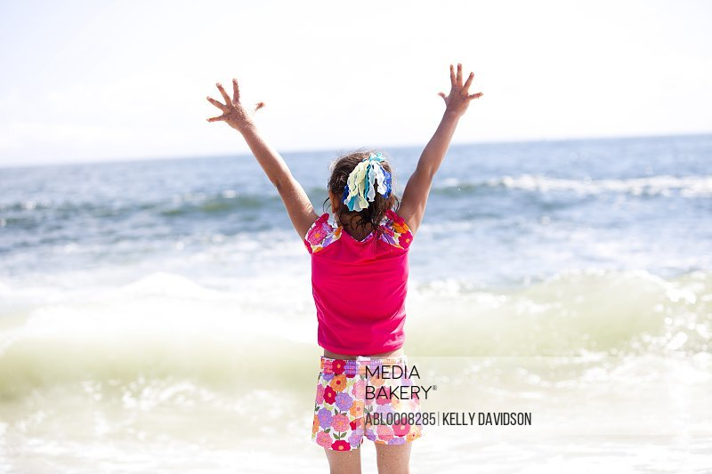 Girl with Arms Outstretched Facing Ocean