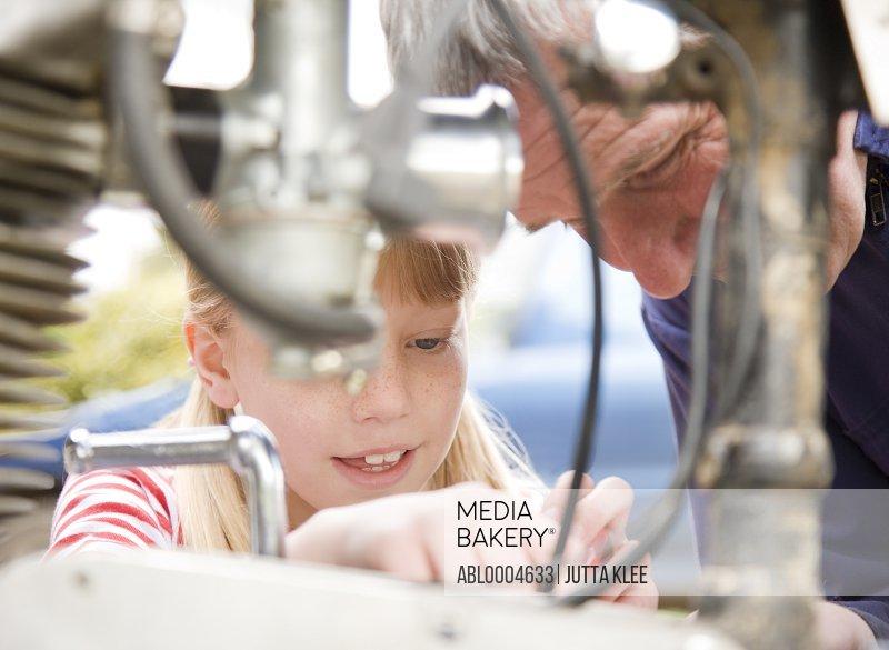 Young girl helping grandfather repairing motorbike engine