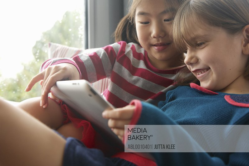 Young Girls Using Digital Tablet Smiling