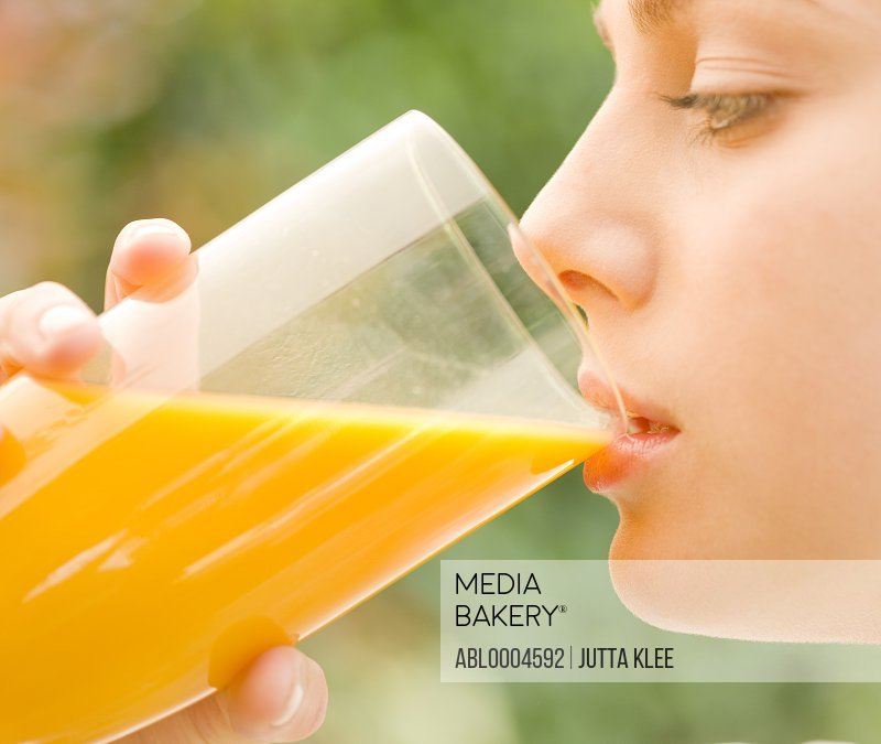 Close up of a young woman drinking and holding a glass of orange juice - profile