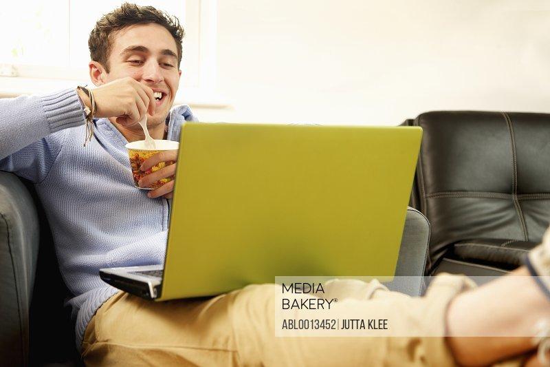 Smiling Man Using Laptop whilst Eating