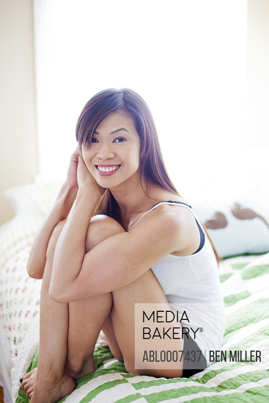 Woman Sitting on Bed with Arms Around Knees