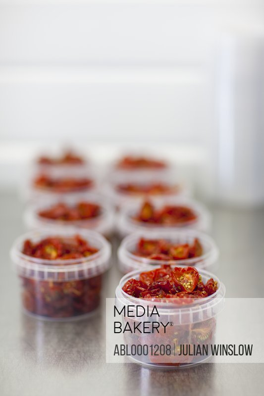 Plastic containers filled with sun dried tomatoes