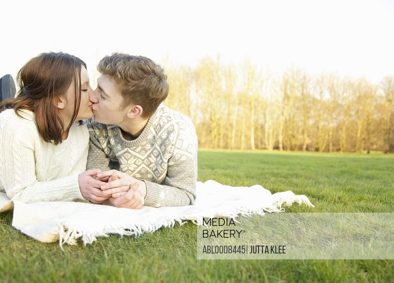 Young Couple lying on Grass Kissing