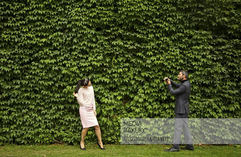 Man Videoing Woman with Camcorder in front of Green Leafy Hedge