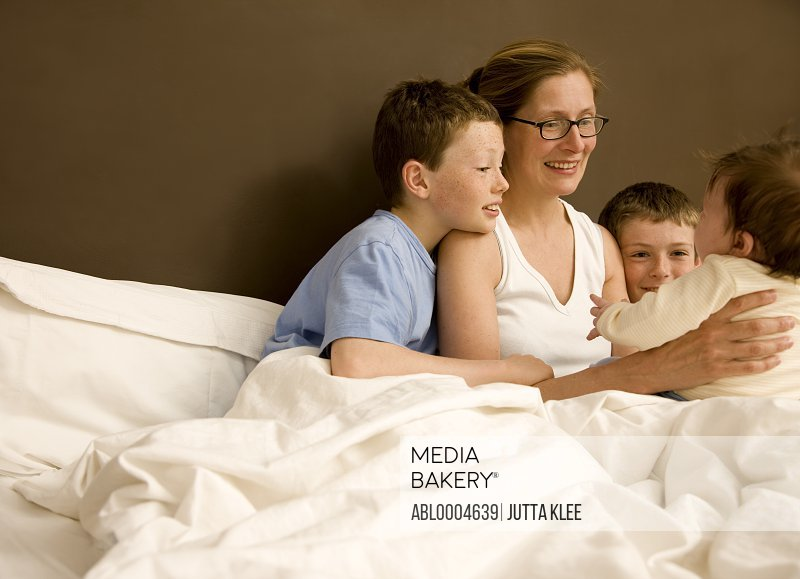 Portrait of a woman in bed with her children and newborn baby