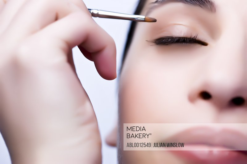 Extreme close up of a woman applying eyeshadow