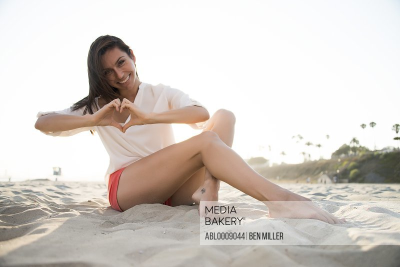 Woman Sitting on Sand Making Heart Shape with her Hands