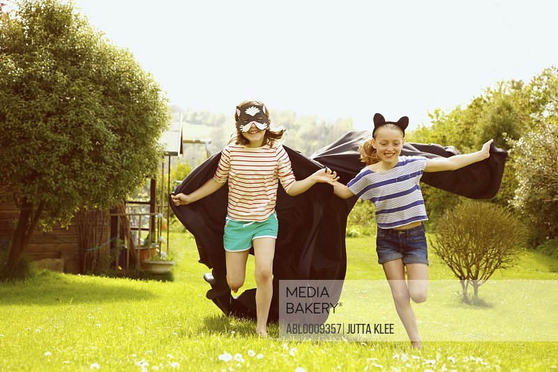 Young Girls Wearing Cape and Mask Running in Garden