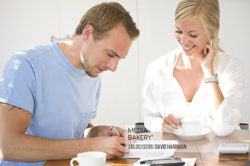 Couple Sitting at Table Signing Paperwork