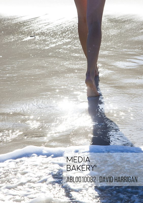 Woman Walking in Sea Water on Beach, Low section