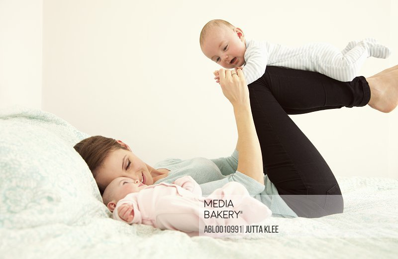 Mother Lying on Bed Playing with Twin Babies