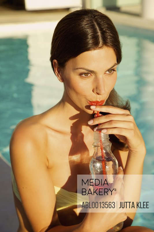 Woman Drinking with Straw by Swimming Pool
