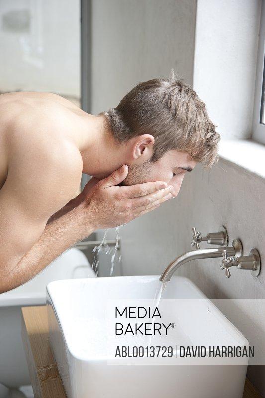 Man Washing Face in Bathroom