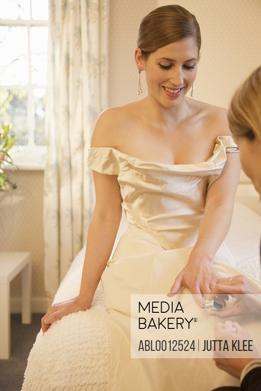 Bride in a white wedding gown sitting on a bed receiving a manicure