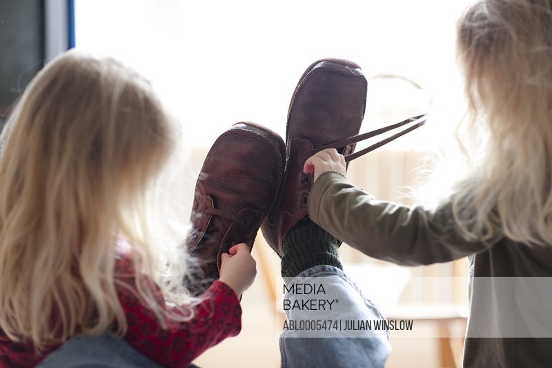 Back view of two girls unfastening a man shoes