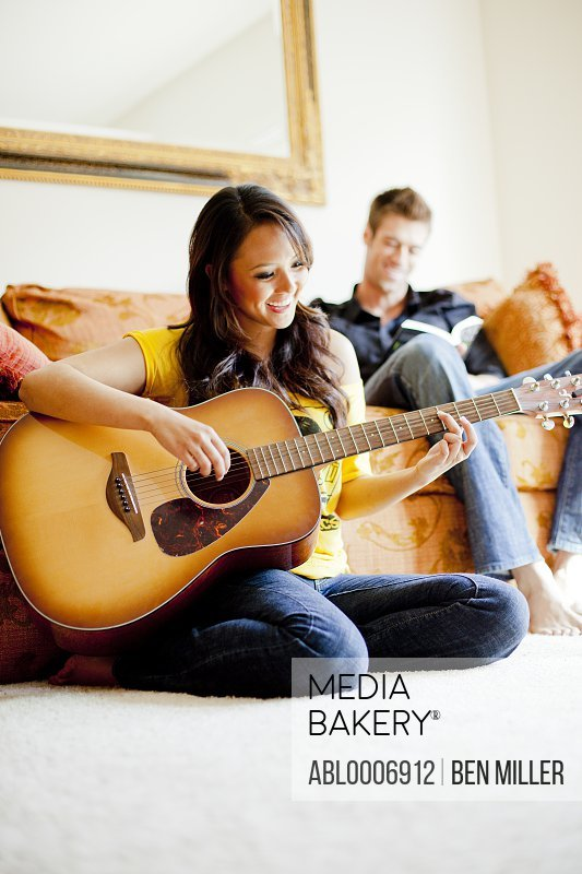 Young Woman Playing Guitar with Man Sitting Behind her Reading