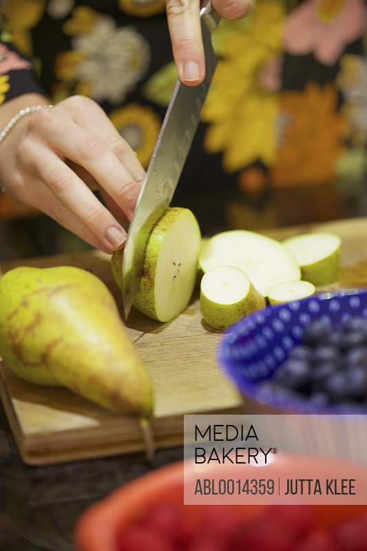Woman Chopping Pear with Knife, Close-up view