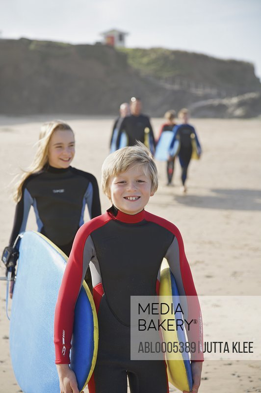 Boy and girl carrying surfboards on a beach followed by people