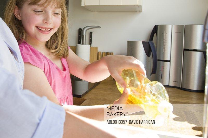 Smiling Girl Squeezing Detergent Bottle