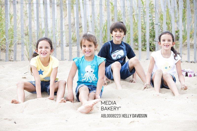 Children Sitting in Sand on Beach