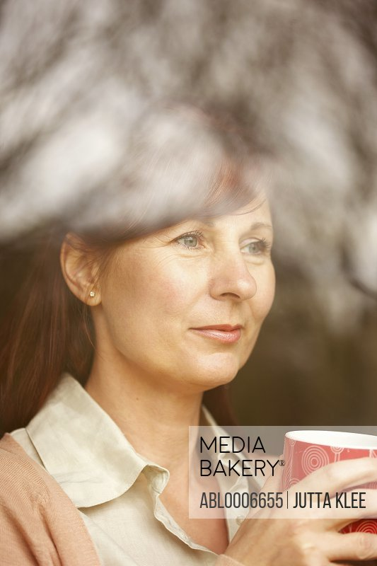 Woman Holding Coffee Cup behind Window