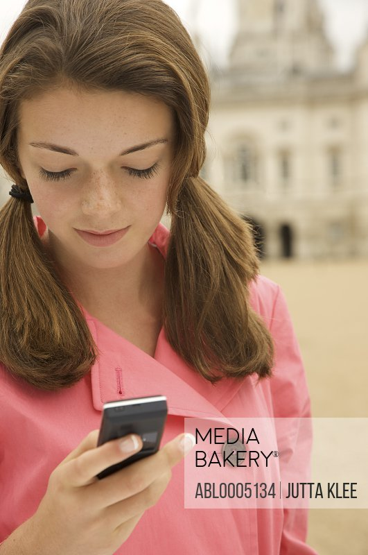 Teenaged girl holding a cell phone in front of London Horse Guards Parade